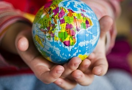 Child's hands holding a world globe
